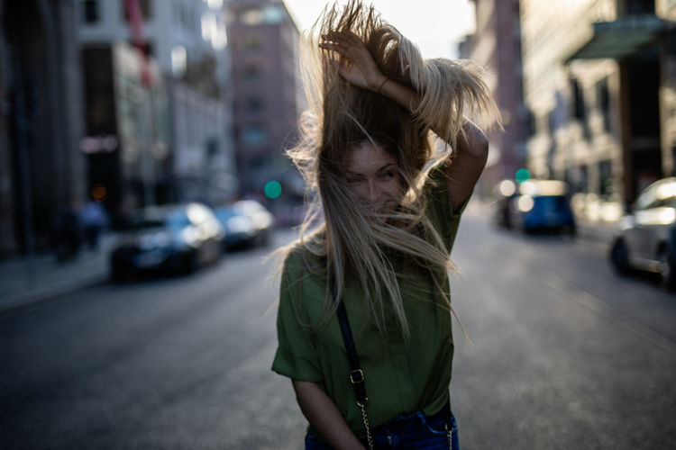 Happy young woman tossing hair while standing on city street