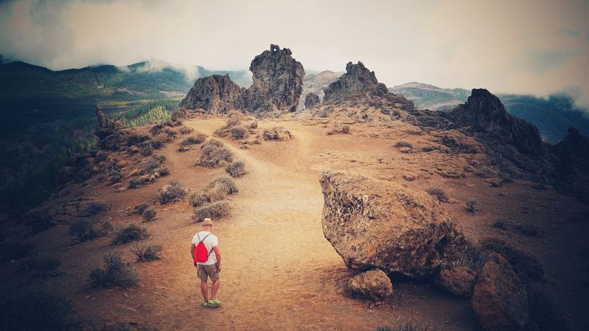 Finding New Frontiers Rock - Object Real People Full Length Rock Formation One Person Nature Beauty In Nature Outdoors Adventure Rear View Hiking Lifestyles Sky Geology Leisure Activity Scenics Landscape Tranquility Day Mountain alone on the top