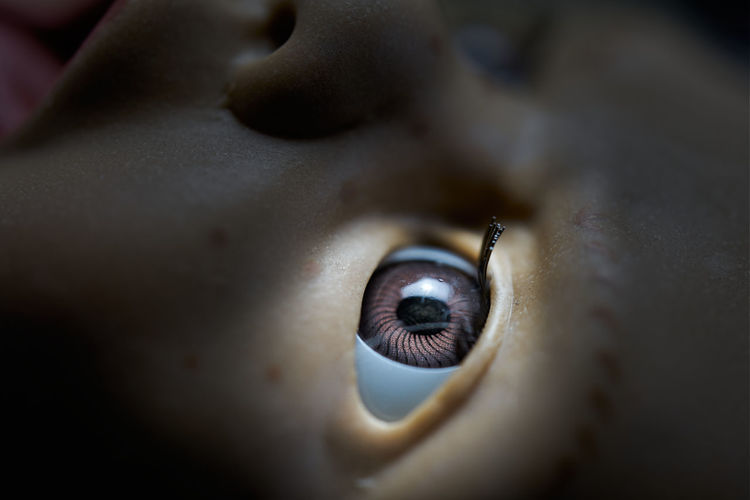 Eye of an old doll in the center of the spotlight, close-up