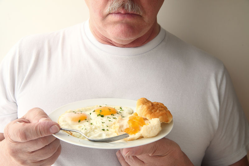 Midsection Of Man Holding Breakfast Plate Against White Background