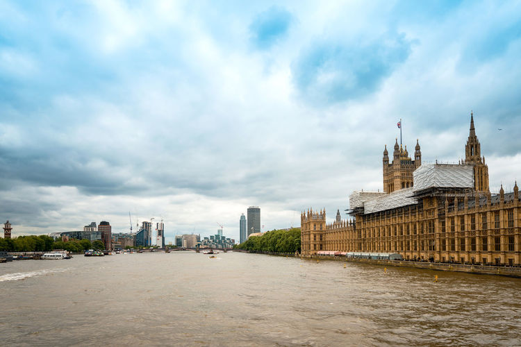 Thames river by houses of parliament in city against cloudy sky