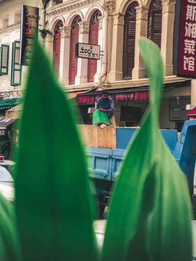 Hardwork in Chinatown Chinatown Singapore Man Street Photography IPhone ASIA Oowa Green Color Focus On Background Day Close-up Building Exterior Outdoors City First Eyeem Photo The Street Photographer - 2018 EyeEm Awards EyeEmNewHere