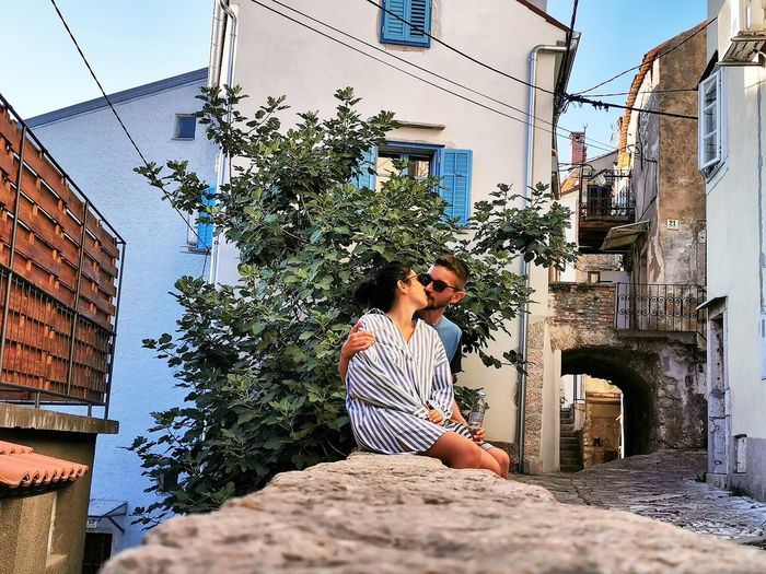 Couple kissing while sitting on retaining wall in city