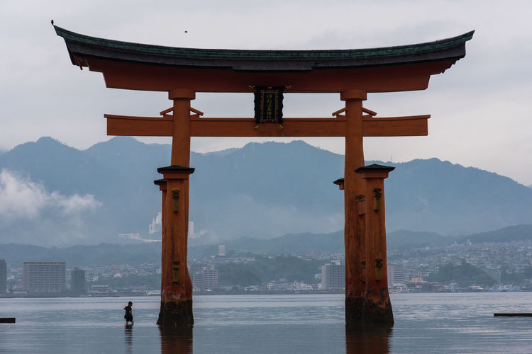 Man By Huge Torii Gate In Sea Against Mountains At Itsukushima Shrine