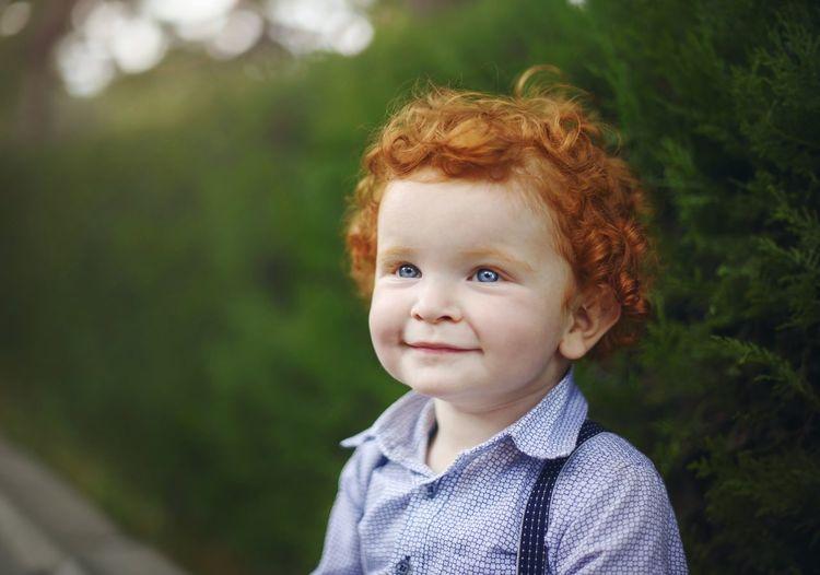Cute smiling boy looking away at park