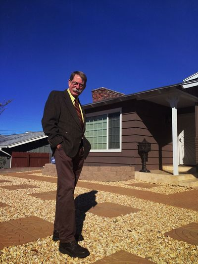 Low angle portrait of senior man standing outside house