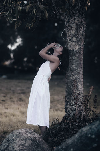 Woman standing by tree trunk in forest
