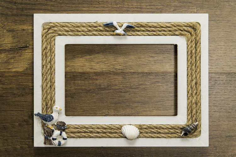 Wooden picture frame with rope decoration around on wooden table Picture Frame Rope Antique Bird Close-up Day Directly Above Frame Indoors  No People Old-fashioned Photo Frame Photo Frames Picture Frame Table Wood - Material Wooden