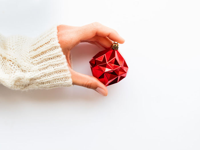 Close-up of hand holding red box against white background