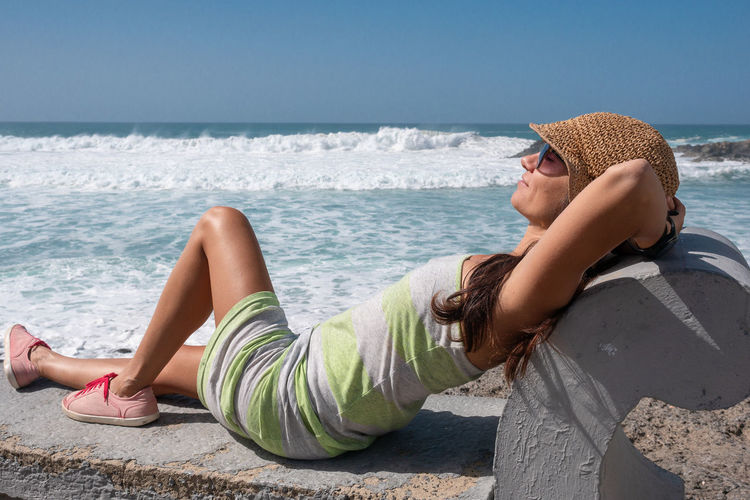 One Person Sea Water Lying Down Relaxation Leisure Activity Nature Land Lifestyles Beach Adult Side View Holiday Young Adult Day Hat Sunlight Women Outdoors Horizon Over Water