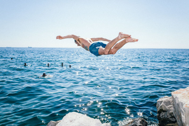 Upside down image of man jumping in sea against clear sky