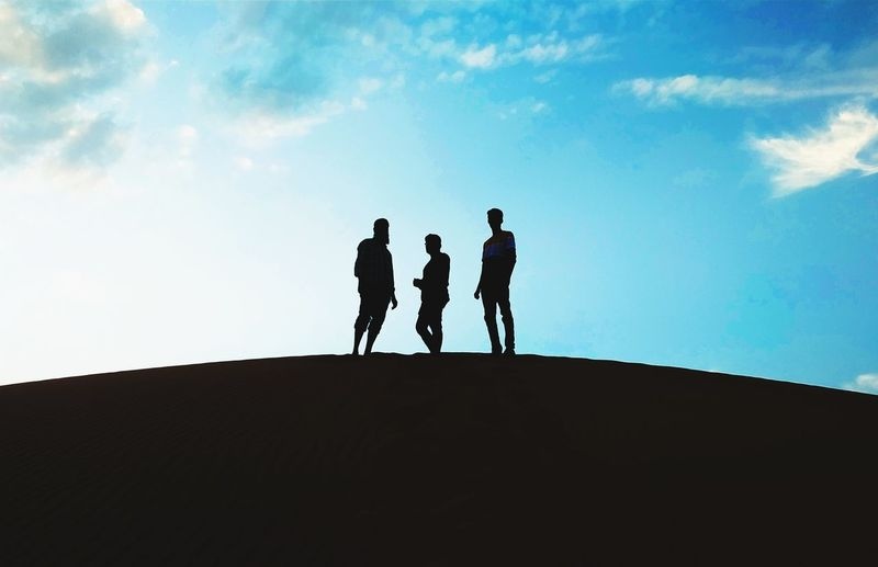 Silhouette friends standing on land against sky