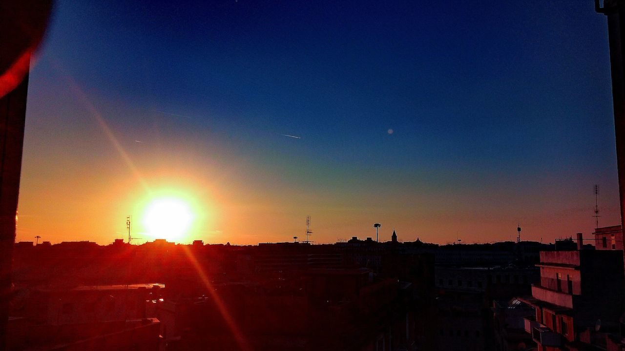 sunset, sun, lens flare, silhouette, sky, sunlight, no people, outdoors, building exterior, nature, architecture, beauty in nature, city, day