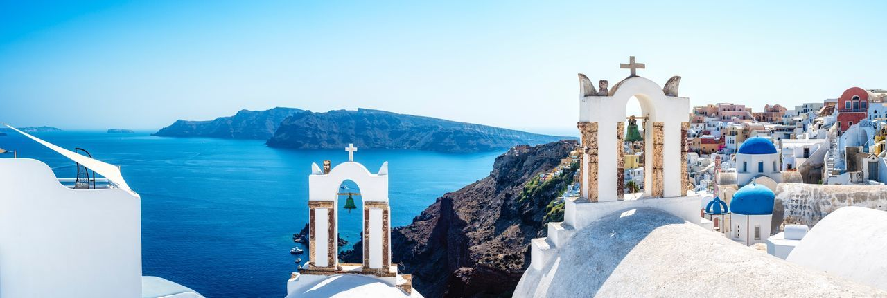 Iconic blue domes and whitewashed houses in Oia, Santorini, Greece with the volcanic caldera and Aegean Sea in the background. Sea Whitewashed Water Architecture Sunlight Panoramic Blue Day Nature Built Structure Sky No People Outdoors Travel Destinations Clear Sky Scenics Aegean Sea Greek Islands Travel Photography Vacation Destination Panorama Church Summer EyeEm Selects EyeEmNewHere