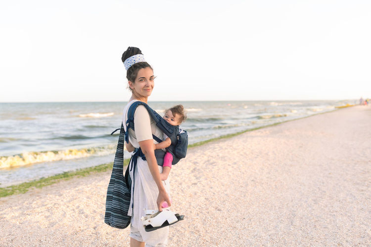 Portrait Of Mother Carrying Daughter While Standing At Beach Against Sky