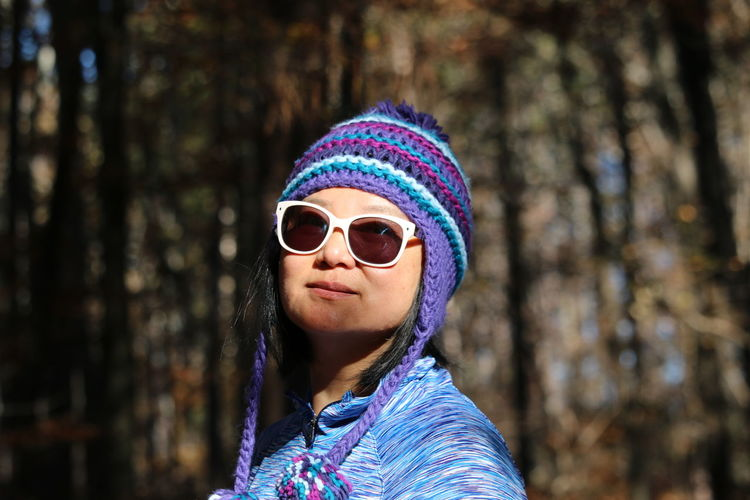 Portrait of woman wearing sunglasses against trees in forest