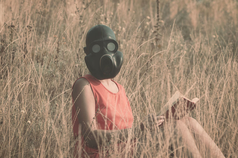 Portrait of woman wearing gas mask while holding book by plants