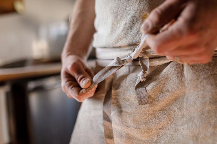 Midsection of woman tying apron in kitchen