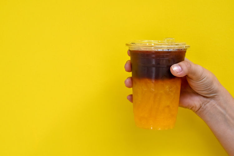 Close-up of hand holding drink against yellow background