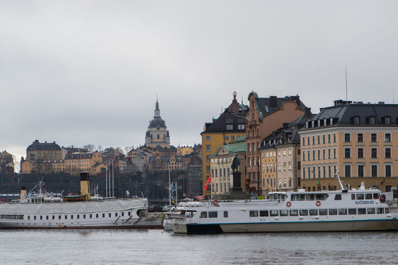 Boats in river with buildings in background