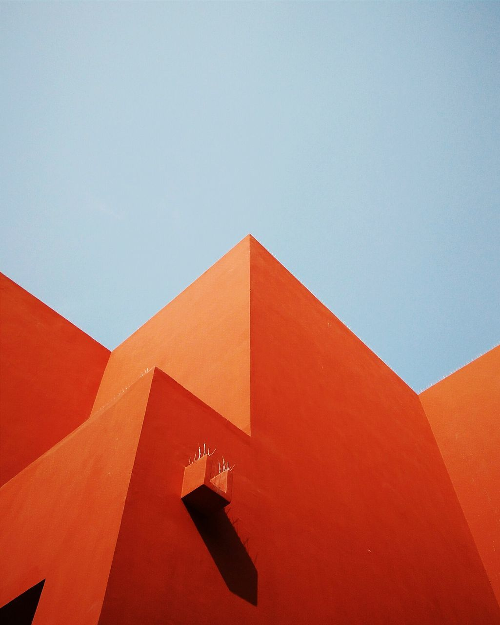 architecture, sky, built structure, nature, copy space, clear sky, low angle view, building exterior, day, no people, blue, sunlight, outdoors, orange color, red, wall - building feature, building, shape, geometric shape, shadow
