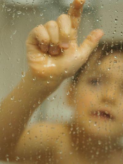 Close-Up Of Cute Boy In Bathroom Seen Through Wet Glass