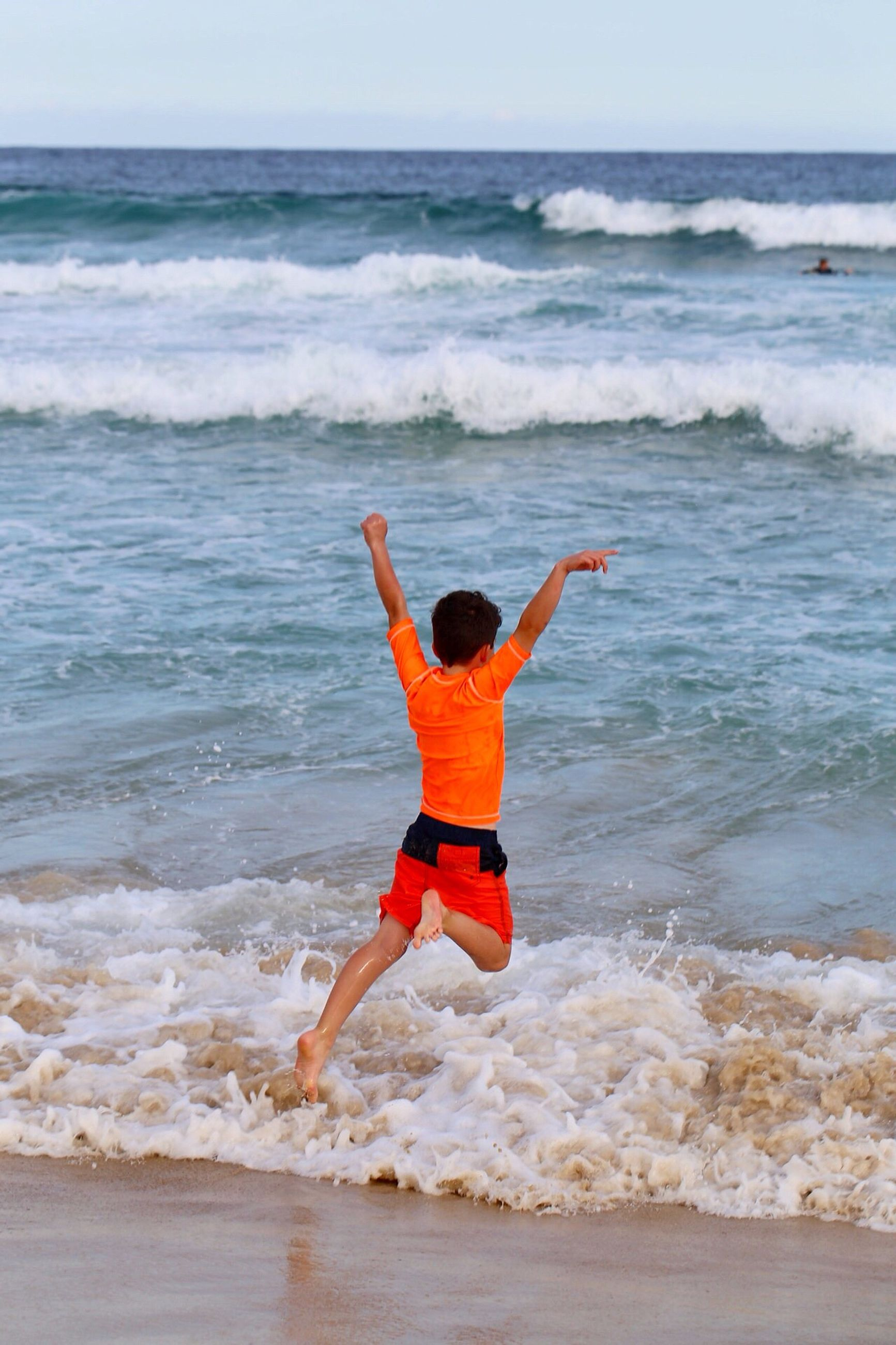 sea, beach, one person, wave, excitement, full length, limb, arms raised, horizon over water, water, healthy lifestyle, happiness, outdoors, motion, people, sand, human arm, day, human body part, one man only, sky, adult, young adult, only men, adults only
