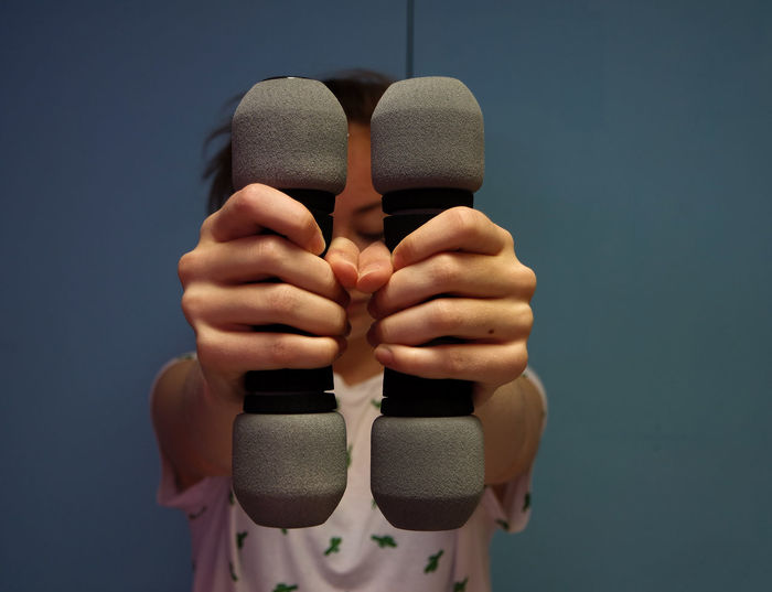 Close-Up Of Woman Holding Dumbbell Against Wall