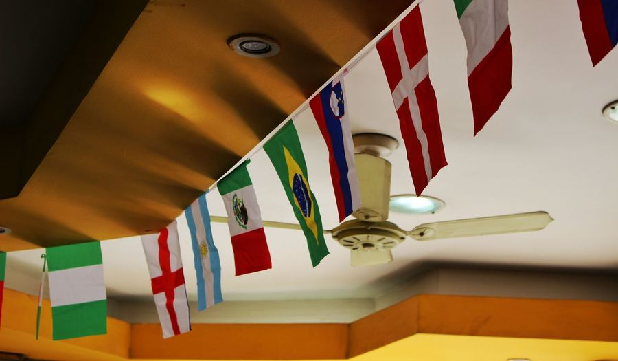 Low angle view of various flags hanging to ceiling