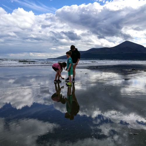 Family standing at beach against cloudy sky