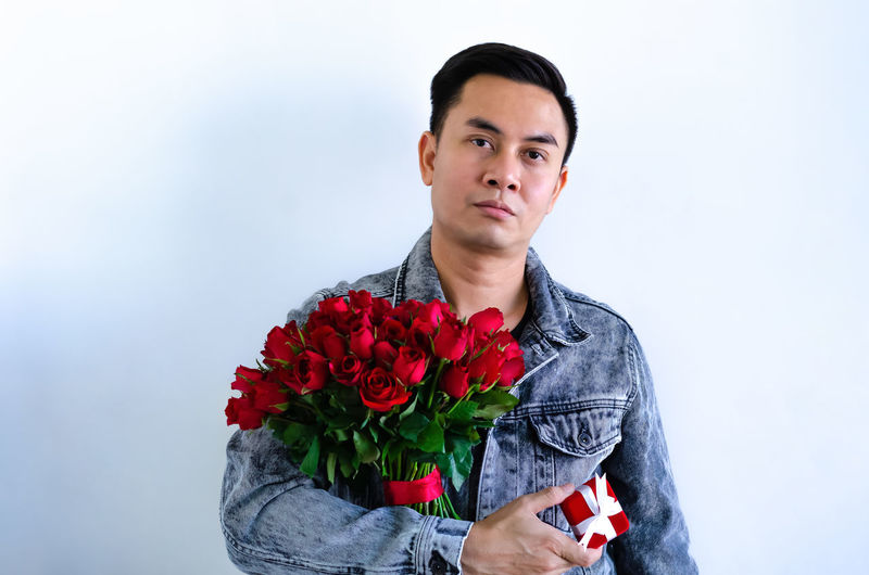 Portrait of young man holding red rose