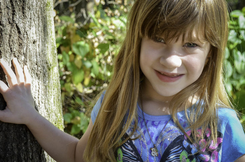 Portrait of smiling girl with tree trunk