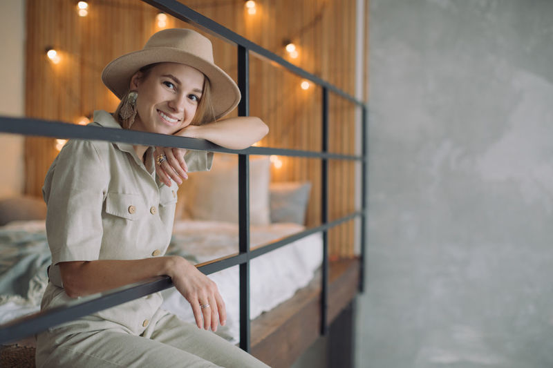 Portrait of smiling young woman holding hat