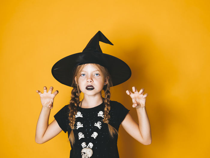 young halloween witch on orange background with black hat Halloween Halloween EyeEm Halloween Horrors Halloween_Collection Arms Raised Celebration Child Childhood Clothing Costume Front View Girl Girls Halloween Hat Human Arm Indoors  Innocence Lifestyles Mouth Open One Person Orange Background Real People Standing Waist Up Witch Women Yellow Yellow Background