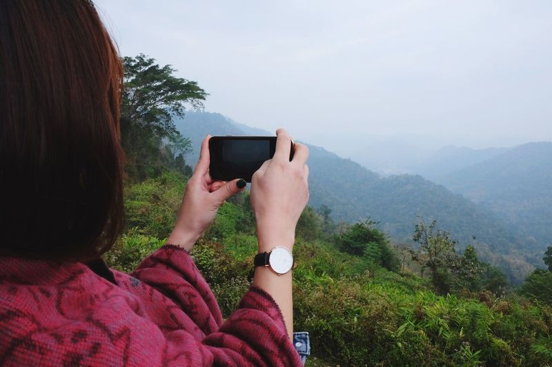 Woman photographing through mobile phone against sky