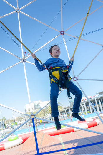 A young boy bounces on a trampoline while attached to bungie ropes. Adventure Blue Sky BOUNCE Bouncing Boy Bungie Child Childhood Clear Sky Day Energetic Exercise Fun Happiness Happy Jump Jumping Lifestyles Low Angle View One Person Outdoors Outside Sky Trampoline Young