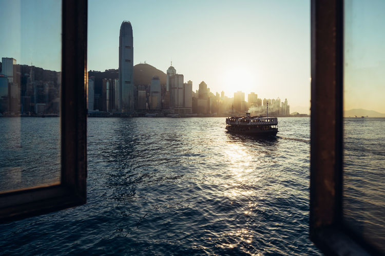 Architecture Boat Built Structure City City Life Cityscape Hong Kong HongKong No People Outdoors Reflection Sky Sun Sunlight Sunset Tourism Water Waterfront