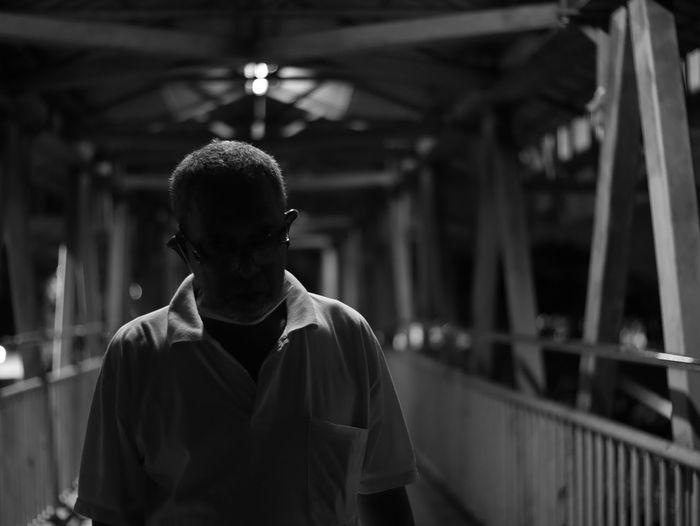 Senior man standing on footbridge at night