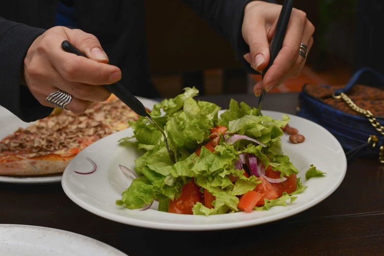 Midsection Of Person Having Salad Served On Table