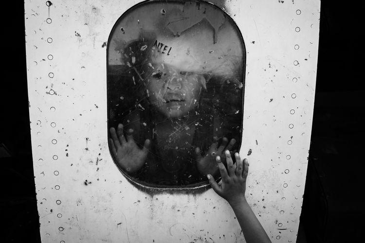 Portrait of woman seen through wet glass