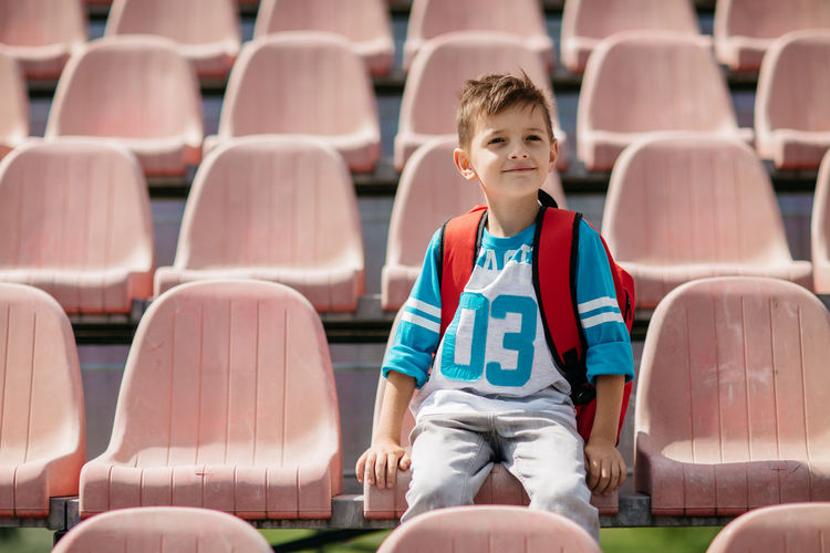 Boy sitting on chair at stadium