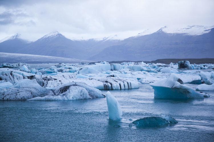 Icebergs in lake against sky