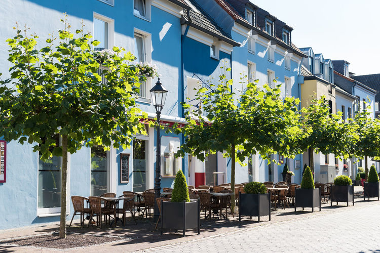 XANTEN, GERMANY - SEPTEMBER 07, 2016: A restaurant has laid the tables outdoors, creating a mediteranian atmosphere A Blue Sky Castel Cathedral Downtown Germany History Medieval Photography Place To Visit Roman Tour Touristic Attratio Xanten
