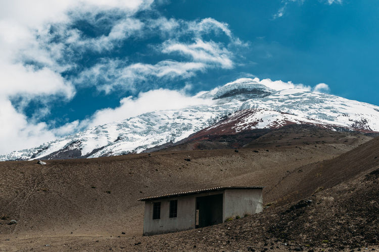 House on snowcapped mountain against sky