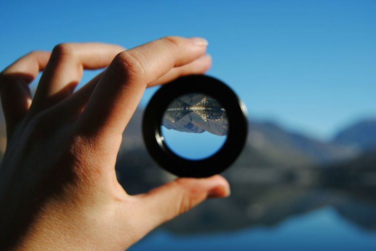 Cropped hand holding lens with upside down reflection of mountains