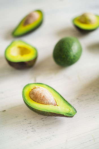 Close-Up Of Avocados On White Table Food And Drink Food Healthy Eating Freshness Wellbeing Still Life Avocado Fruit Green Color Table Indoors  Halved SLICE Close-up No People Cross Section Seed High Angle View Group Of Objects Focus On Foreground Temptation