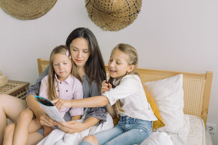 Siblings with mother sitting at home