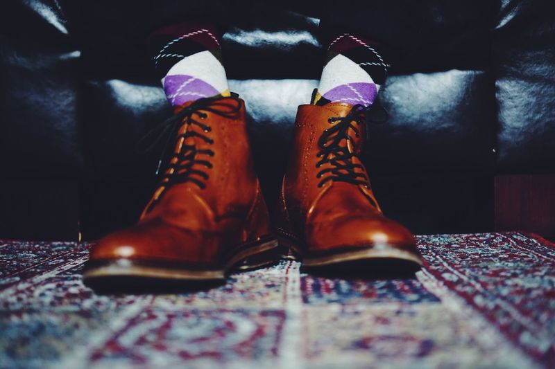 Low section of man wearing leather shoes on carpet