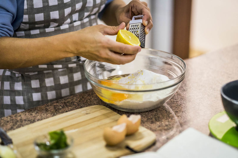 woman scratch lemon to put in the dough Bakery Bowl Close-up Day Dough Egg Yolk Eggs Flour Food Food And Drink Freshness Healthy Eating Holding Human Hand Indoors  Ingredient Lemon Lifestyles Midsection Mixing Mixing Bowl One Person People Preparation  Table