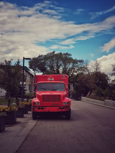 Red truck on road against sky in city